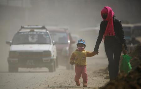 काठमाडौंको धूलोमा मास्क लगाएर हिँड्दै। फाइल तस्बिरः रोयटर्स